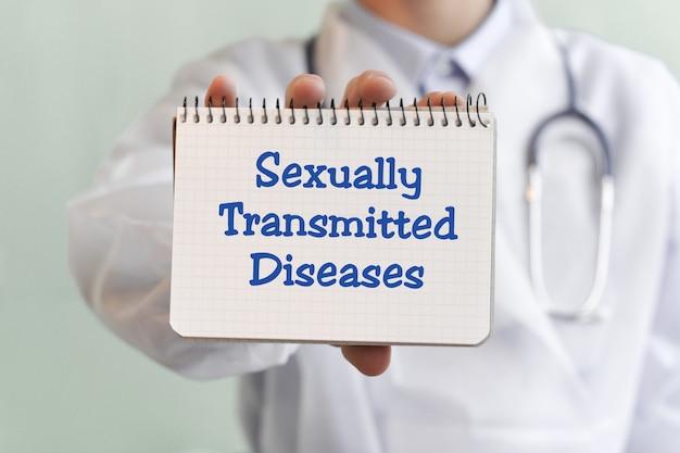 Médico escrevendo palavras doenças sexualmente transmissíveis com marcador blu, conceito médico