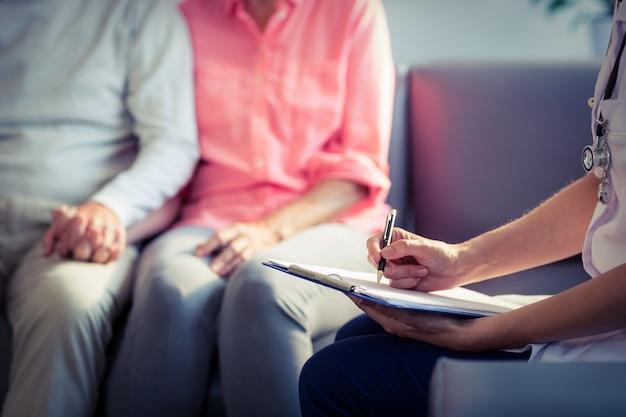 Médico escrever relatório médico do casal sênior