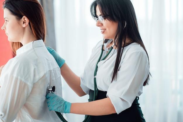 Médico escuta o paciente usando um estetoscópio