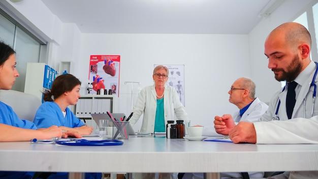 Médico especialista discutindo com a enfermeira durante o brainstorming médico sobre novas tecnologias na medicina. terapeuta clínico com colegas falando sobre doença, especialista, especialista, comunicação.