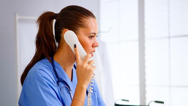 Médico especialista em enfermagem, verificando consulta durante a comunicação de telessaúde no hospital. médico da saúde em uniforme de remédio, assistente médico da recepcionista ajudando na consulta ao telefone