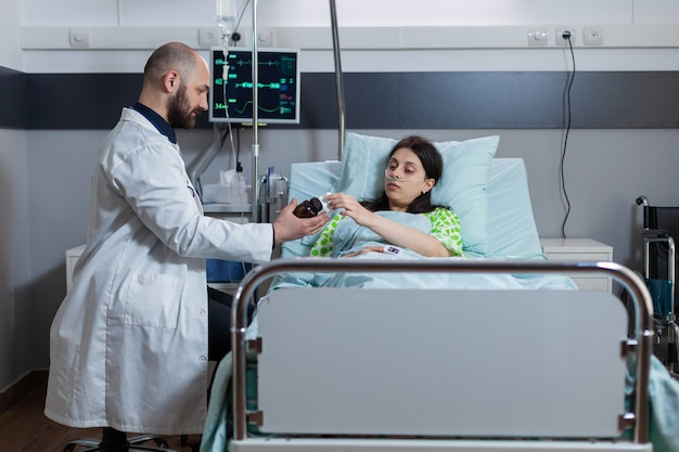 Médico especialista em verificação de mulher doente durante consulta médica em enfermaria de hospital médico medic di ...