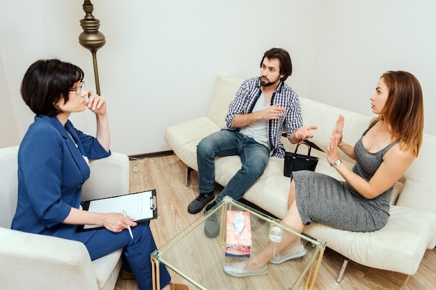 Médico esperto está sentado na frente do casal e ouvindo o que eles estão falando. guy está apontando para sua esposa e culpando-a. ela não concorda com ele.