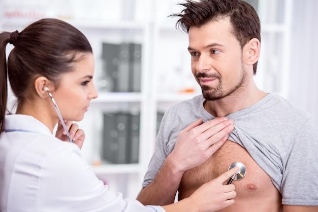 Médico está examinando os pulmões do paciente com um estetoscópio.