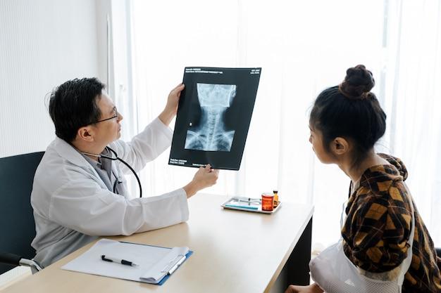 Médico está explicando sobre os resultados de raios-x do cérebro para uma paciente do sexo feminino em seu escritório em ho