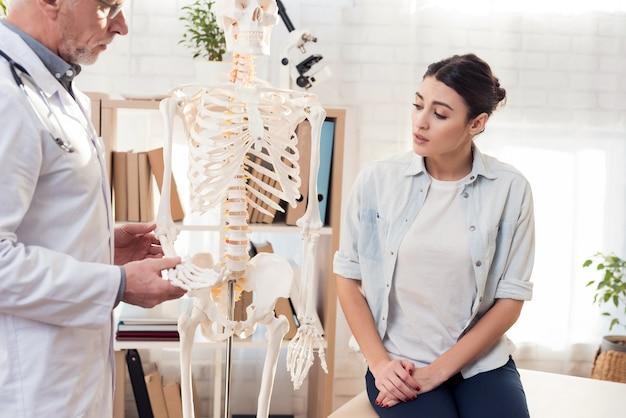 Médico está mostrando a mão do esqueleto na clínica.