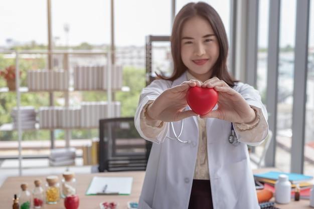 Médico está mostrando um coração vermelho no escritório