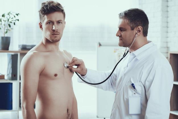 Médico está ouvindo o batimento cardíaco com estetoscópio.