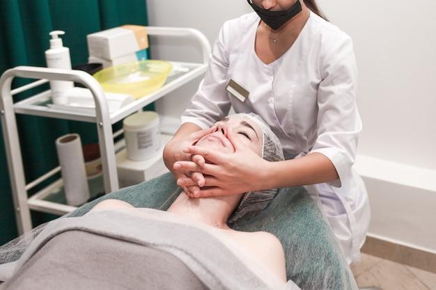 Médico esteticista faz massagem facial cosmética. a mulher relaxa em uma vista lateral da cadeira cosmética