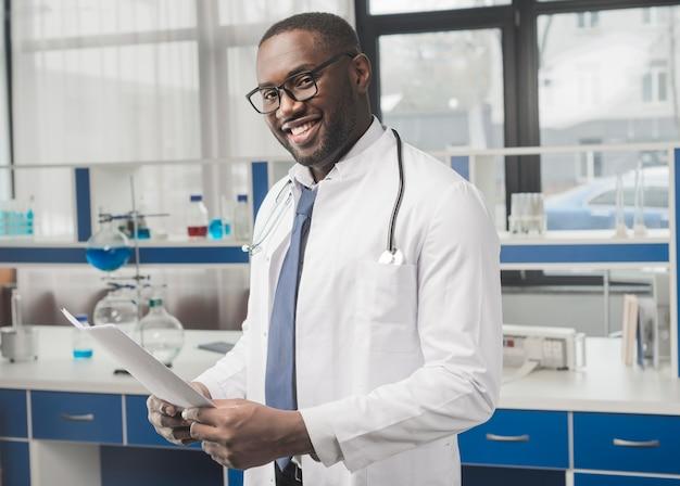 Médico étnico alegre com papéis