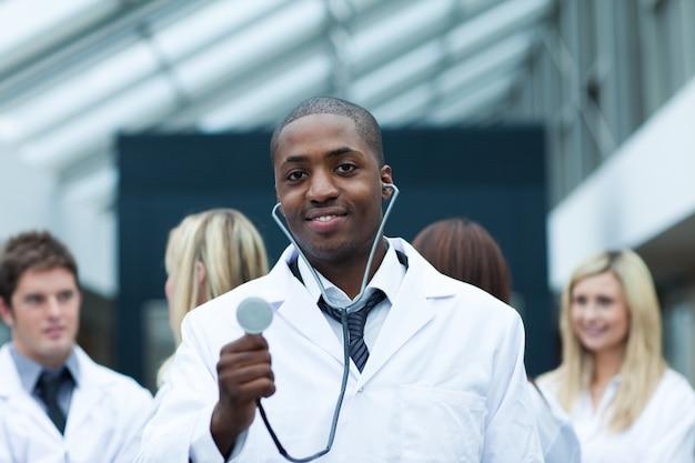Médico étnico com sua equipe em segundo plano