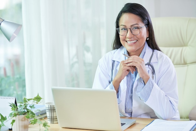 Médico étnico sorridente, sentado na mesa no escritório