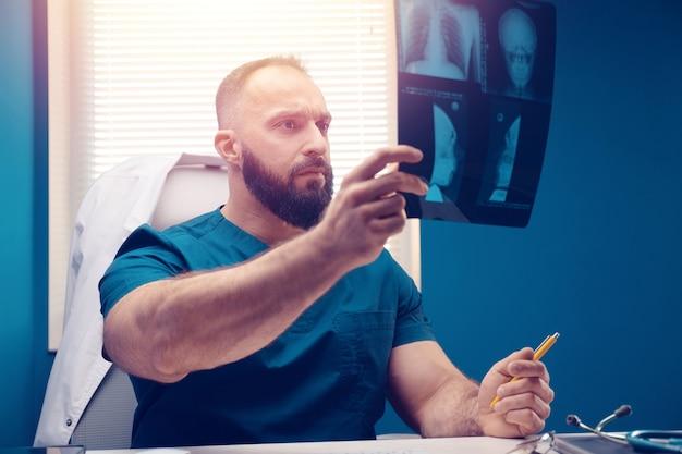 Médico examina o raio x e ressonância magnética no escritório