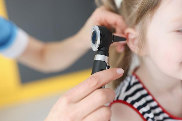 Médico examina o tímpano de uma menina