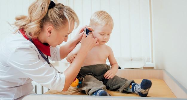 Médico examina orelha com otoscópio em uma sala de pediatra.