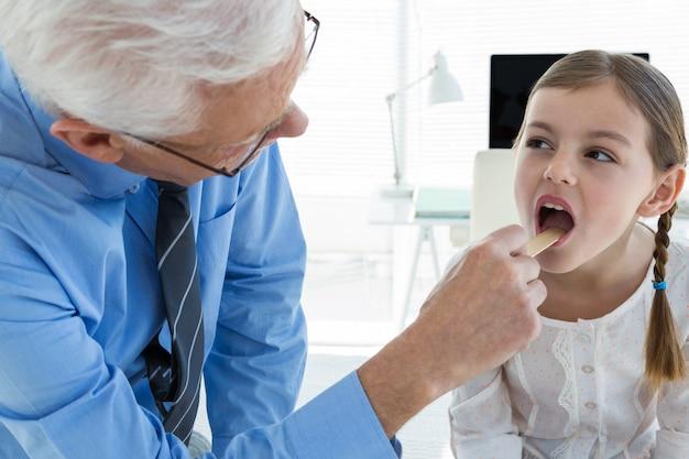 Médico examinando a garganta do paciente usando um abaixador de língua