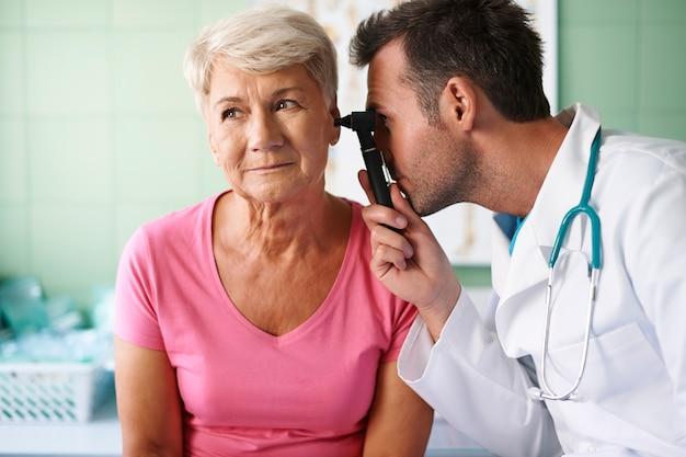 Médico examinando a orelha de uma mulher idosa