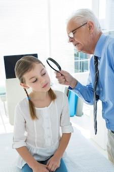 Médico examinando o ouvido do paciente usando lupa
