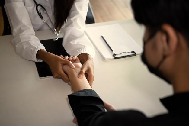 Médico examinando o pulso dos pacientes com as mãos na sala médica.