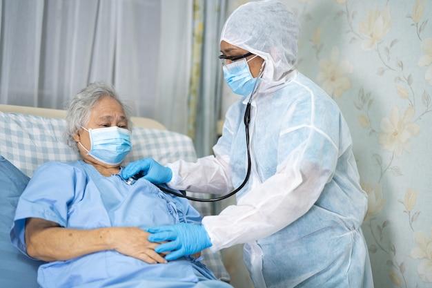 Médico examinando paciente asiática sênior usando máscara facial