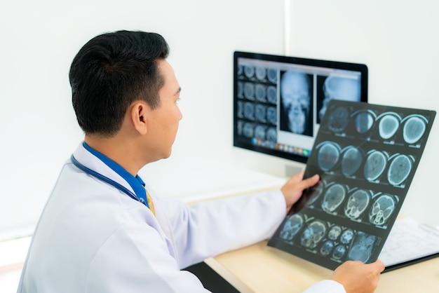 Médico examinando raio x do crânio do paciente