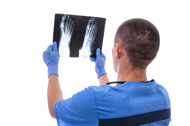 Médico examinando raio-x. ele está segurando e olhando para ele isolado no branco
