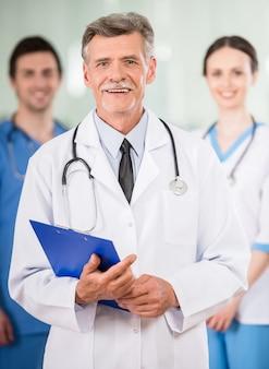 Médico experiente com jovens colegas no consultório médico.
