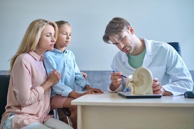 Médico experiente explicando os fundamentos da anatomia do ouvido humano para uma garota séria e sua mãe
