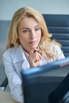 Médico experiente olhando atentamente para o monitor do computador