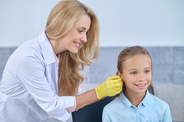 Médico experiente sorridente em luvas esterilizadas inserindo um aparelho surdo no canal auditivo de um paciente jovem