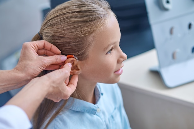 Médico experimentando aparelho auditivo para menina
