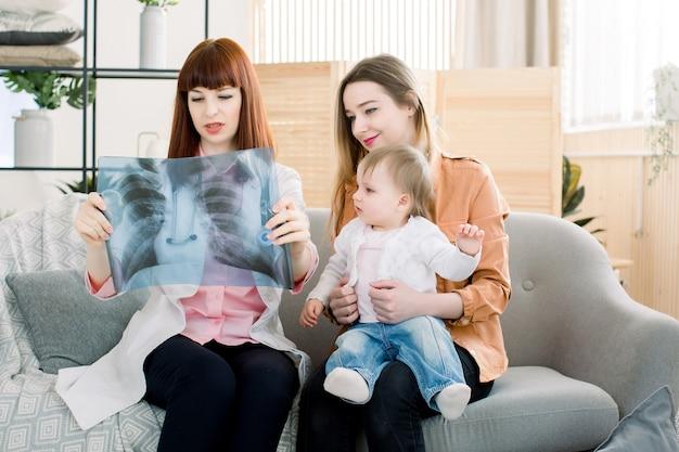 Médico, explicando a imagem de raio-x do peito para mãe com filha, sentado no sofá cinza na clínica