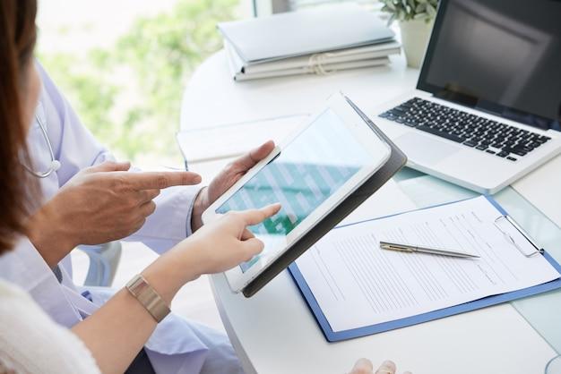 Médico explicando ao paciente como preencher dados pessoais em formulário no tablet digital