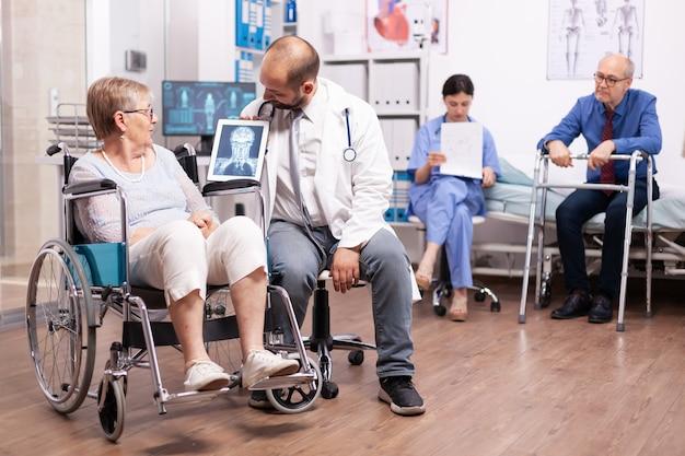 Médico explicando diagnóstico para mulher idosa com deficiência em cadeira de rodas