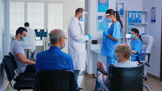 Médico explicando o diagnóstico do paciente para uma das enfermeiras usando máscara de proteção contra covid-19 na área de espera do hospital. homem maduro, discutindo com uma mulher deficiente em cadeira de rodas.
