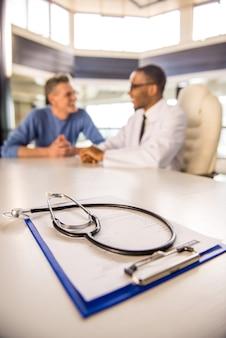 Médico fala com seu paciente na clínica.