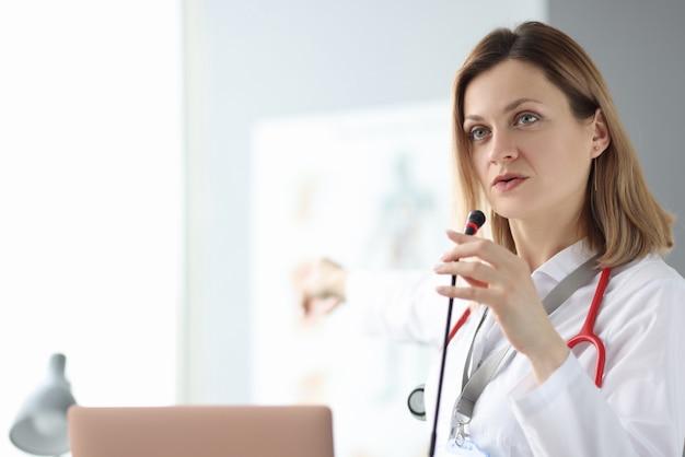 Médico falando ao microfone no seminário de treinamento
