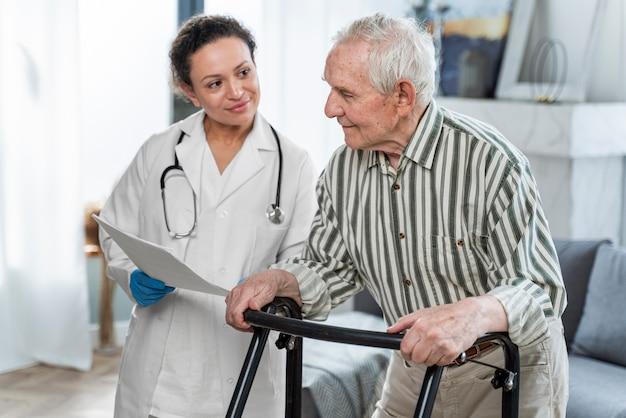 Médico falando com homem sênior dentro de casa