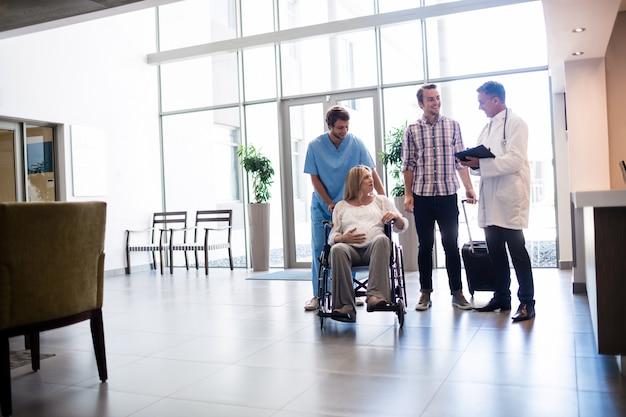 Médico falando com mulher grávida em cadeira de rodas