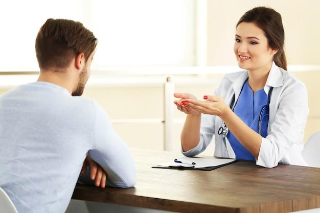 Médico falando com paciente do sexo masculino na sala com luz