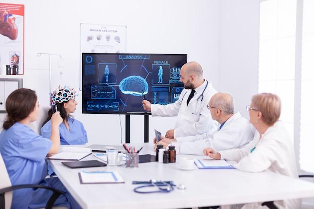 Médico falando sobre a atividade cerebral durante a conferência com a equipe médica e enfermeira usando fone de ouvido com sensores. o monitor mostra um estudo moderno do cérebro enquanto a equipe de cientistas ajusta o dispositivo.