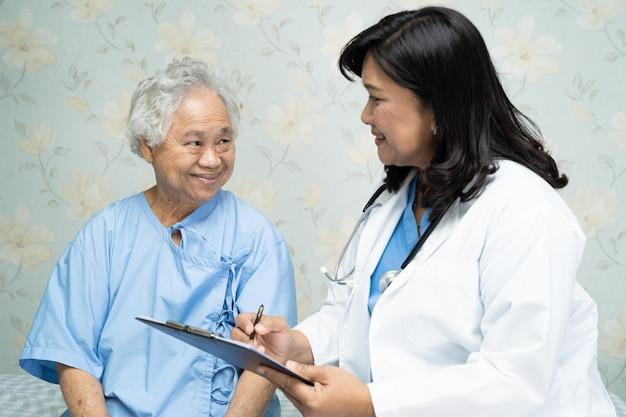 Médico falando sobre diagnóstico com mulher asiática idosa no hospital