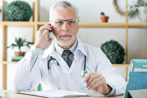 Médico, falando telefone, e, olhando