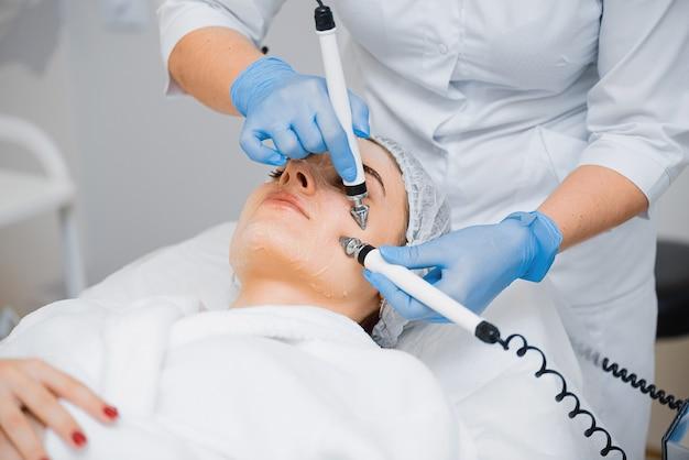 Médico faz massagem facial para uma jovem usando microcorrentes.