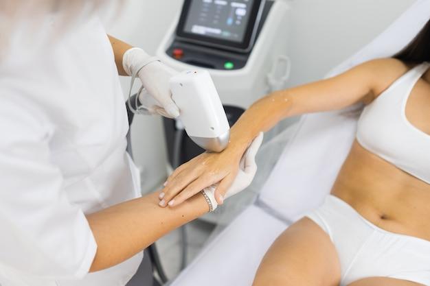 Médico faz para mulher procedimento de depilação a laser
