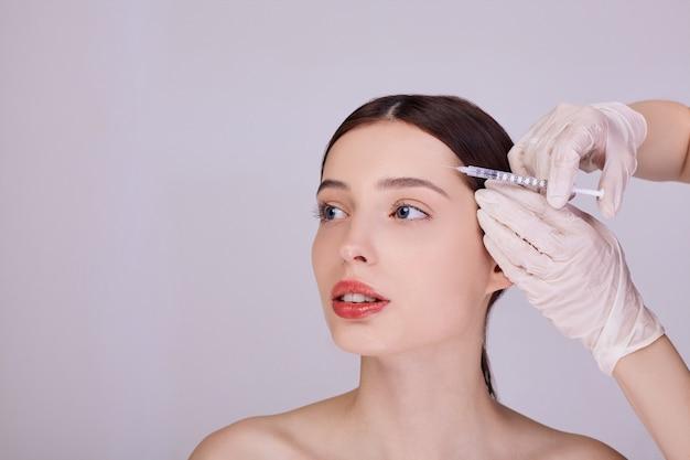 Médico faz uma injeção na testa de uma jovem mulher