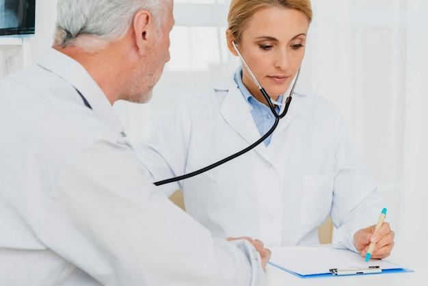 Médico fazendo anotações enquanto ausculta