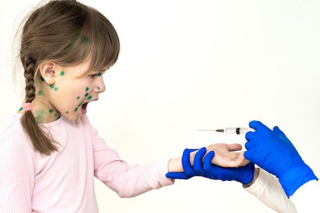 Médico fazendo injeção de vacinação em uma menina criança com medo de varicela, sarampo ou vírus da rubéola