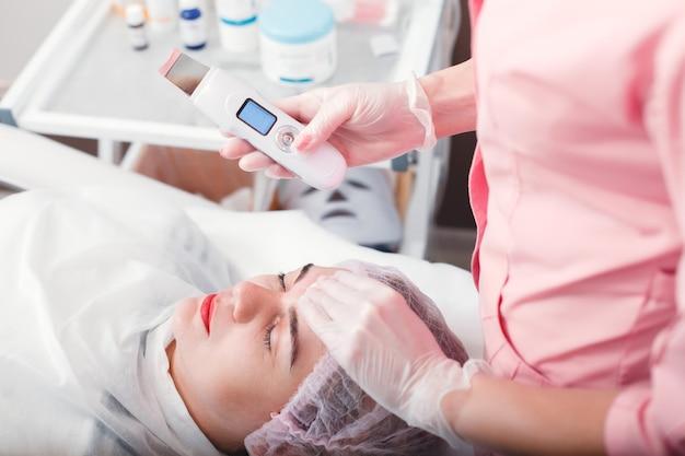 Médico fazendo procedimento médico com a pele do rosto. terapia de limpeza ultrassônica. tratamento cosmetológico. saúde.