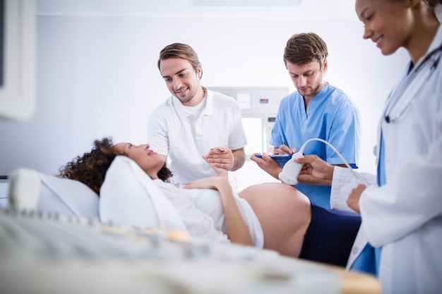 Médico fazendo ultra-sonografia para mulher grávida